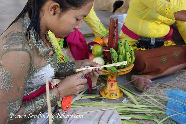 A young girl makes a palm weaving for a temple offering