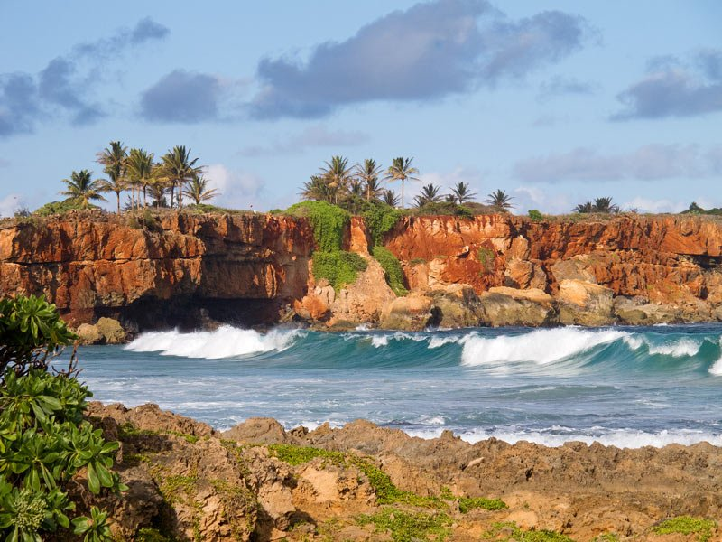 An incredibly scenic hiking trail leading from the Grand Hyatt Kauai winds along red cliffs.