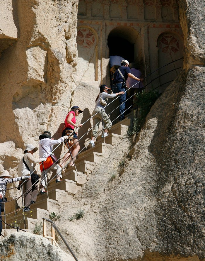Visitors climb up the steps of a rock-cut church in the Goreme Museum