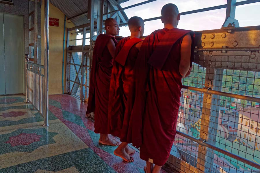Monks wait to take the elevator back down from the Shwesandaw Pagoda