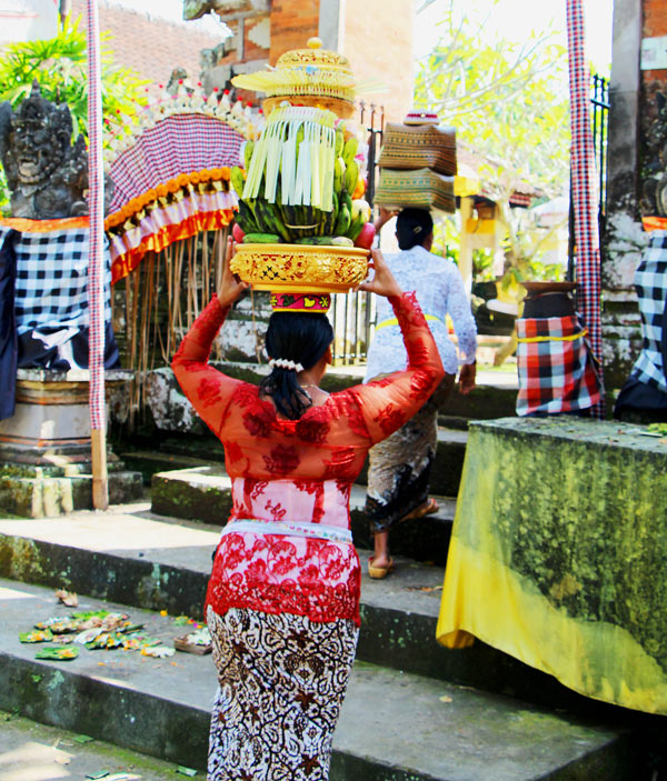 A woman carries fruit offerings on her head as she enters a Bali temple
