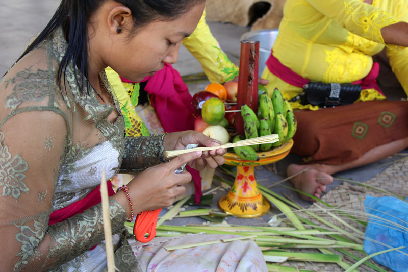 A young girl makes a palm weaving for a temple offering in Bali