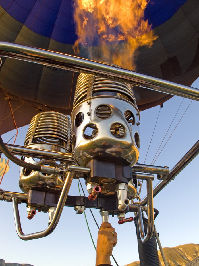 The pilot can make a hot air balloon rise faster by blasting a larger flame to heat the air more quickly