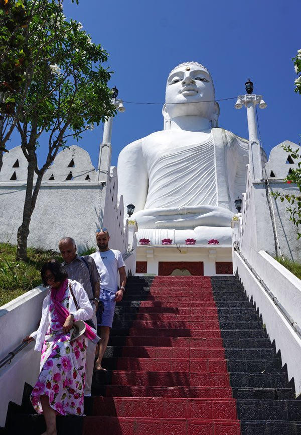 Steep stairs lead up to the giant Kandy Buddha statue rising up above the sacred city