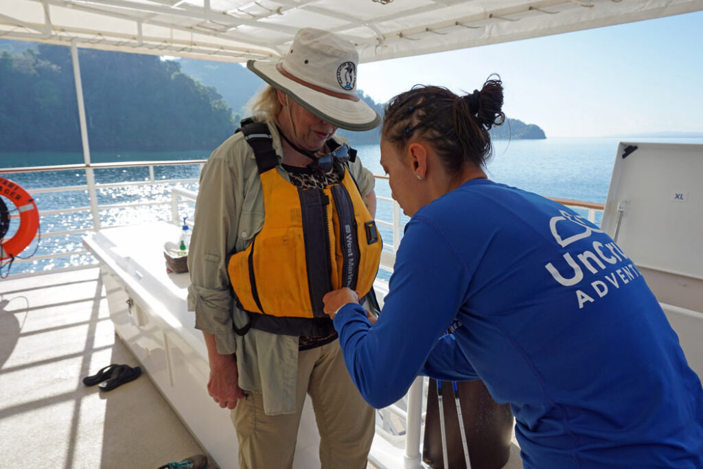 An UnCruise Adventures' staff member helps a guest gear up for a skiff ride in a Zodiac-style inflatable.