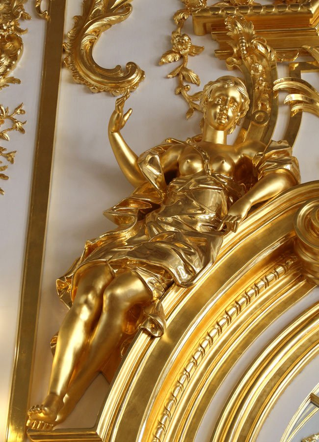 Gold figurines adorn the tops of windows and doors in the Great Hall of Catherine Palace.