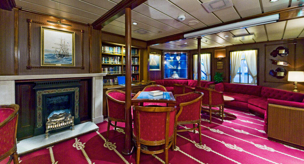 Guests read and play cards in the Star Clippers library.