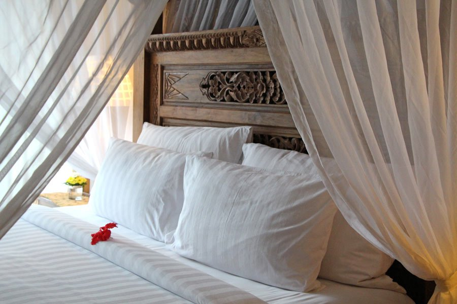 Bedrooms of the wood-carved villas at Ayung Resort Ubud have huge four-poster king beds.