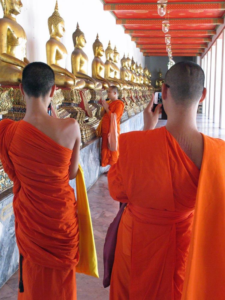 Monks visit and pray at Wat Pho in Bangkok, one of the best places to visit in Thailand.