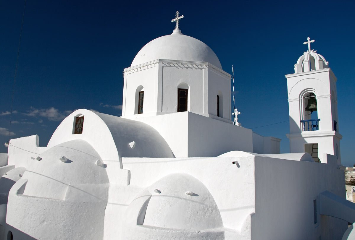 Church domes gleam white in the dark blue Santorini sky