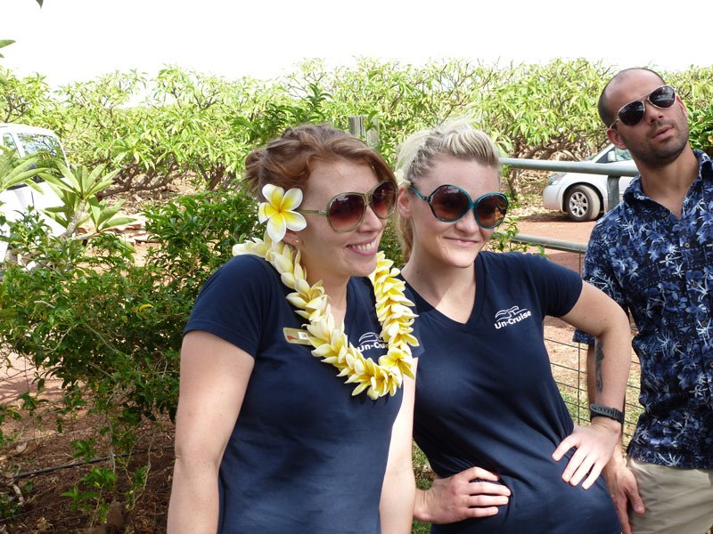 Smiling UnCruise staff show off their plumeria leis in Hawaii