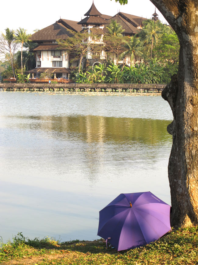 There's a couple kissing behind the umbrella in this Yangon park.
