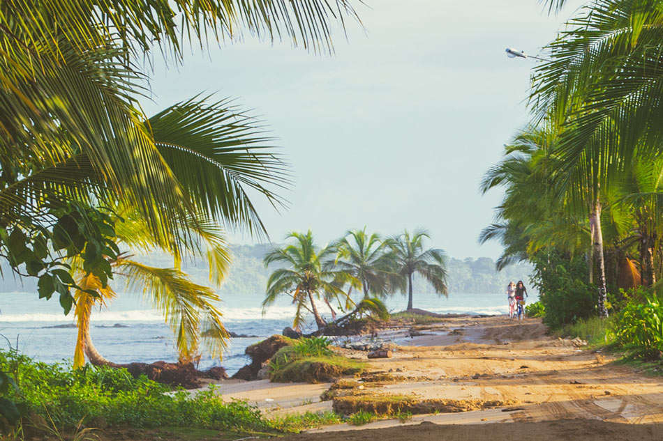 "Visitors bicycle the sand coastal ""road"" on Isla Colon, Bocas del Toro"