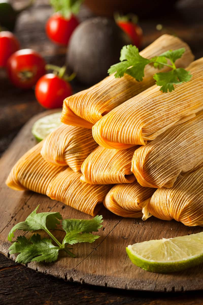 Tamales are a Mexican food dish made of minced meat and corn flour, wrapped in a maize husk.