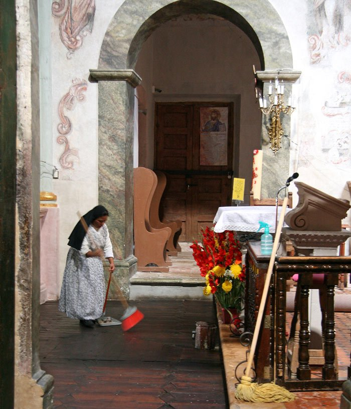 A nun sweeps the floor in front of the altar at the Sanctuary of Atotonilco