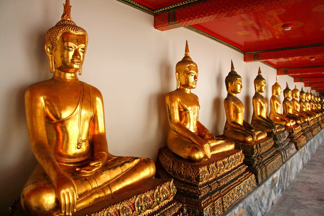 A row of gilded Buddhas at Wat Pho Temple in Bangkok catch the eye.