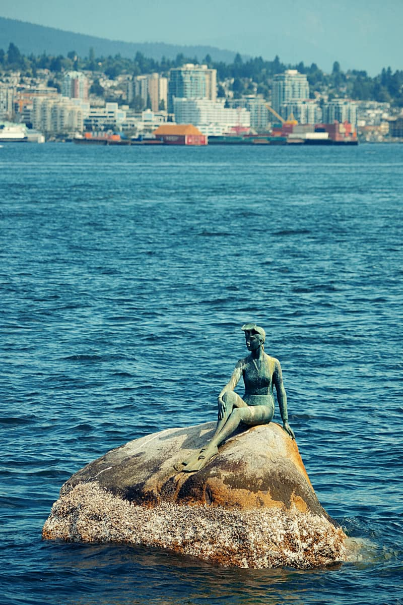 """""""Girl in a Wetsuit"""" gets lots of looks from cyclists biking Stanley Park as she sits on a rock surveying the water."""