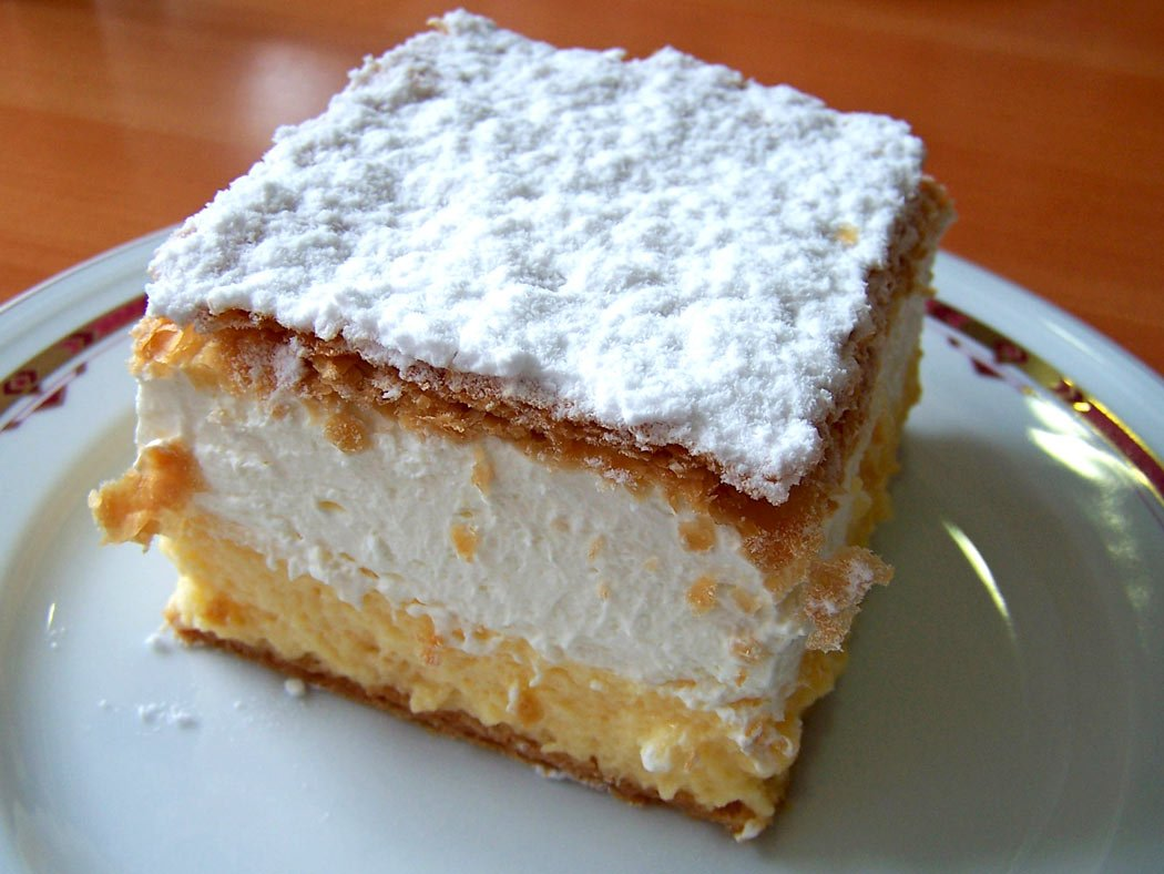 Croatian kremsnita or vanilla custard cake is a delicious sweet made of puff pastry and a whipped egg cream filling, dusted with icing sugar on top.