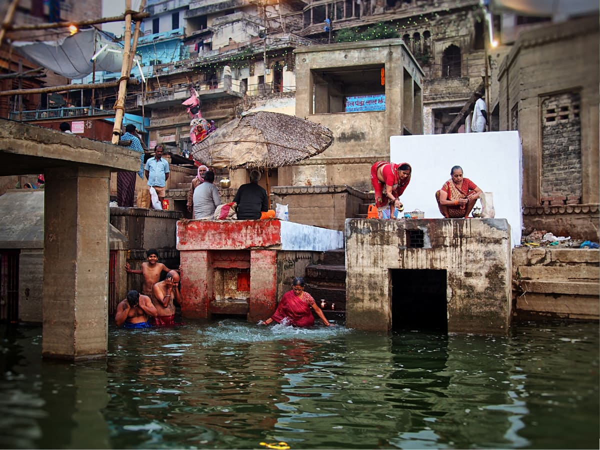 People living alongside the Ganges bathe in and worship by the river, considered holy in Hinduism.